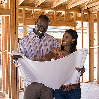 Photo of a young couple looking at building plans